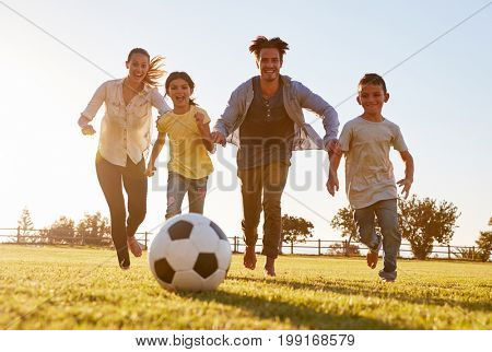 Young family chasing after a football in a park
