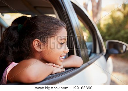 Young black girl looking out of car window smiling, side view