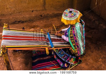 Peruvian woman weaving colorful alpaca wool, using ancient techniques