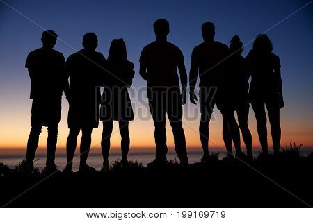 Group of young adults admiring sunset by the sea