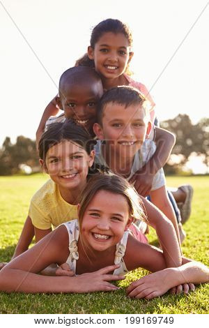Smiling boys and girls lying in a pile on grass in Summer