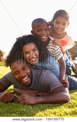 Happy black family lying in a pile on grass outdoors