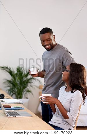 woman working from home laughs and points at computer screen while discussing ideas with husband partner man