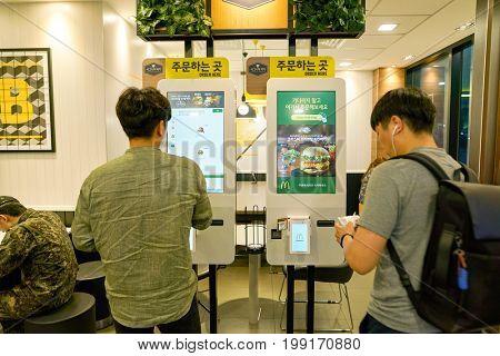 BUSAN, SOUTH KOREA - CIRCA MAY, 2017: people use ordering kiosk at McDonald's restaurant. McDonald's is an American hamburger and fast food restaurant chain.