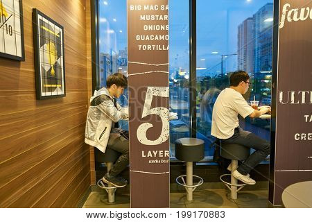 BUSAN, SOUTH KOREA - CIRCA MAY, 2017: people eat at McDonald's restaurant. McDonald's is an American hamburger and fast food restaurant chain.