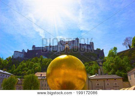 Salzburg, Austria - May 01, 2017: The golden ball statue with a man on the top sculpture, Kapitelplatz Square, Salzburg, Austria on May 01, 2017 against Hohensalzburg Fortress.