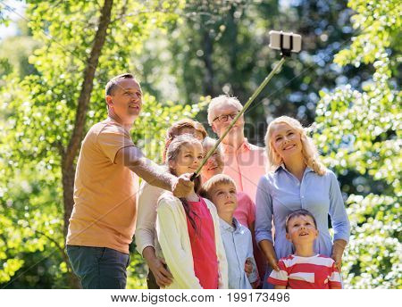 generation and people concept - happy family taking picture with smartphone and selfie stick in summer garden