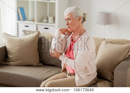 old age, health problem and people concept - senior woman suffering from pain in hand at home