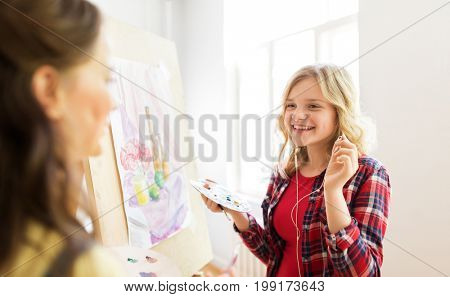 art school, creativity and people concept - happy smiling student girls or artists with earphones, easel and palette painting still life picture at studio