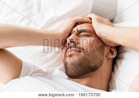 people, bedtime and rest concept - close up of man lying in bed at home suffering from headache or hangover