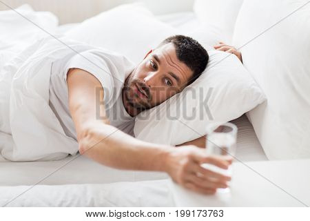 people, bedtime and rest concept - man in bed and reaching to glass of water at home