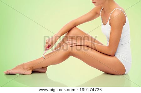 people, beauty, depilation and bodycare concept - beautiful woman with safety razor shaving legs sitting on floor over green background