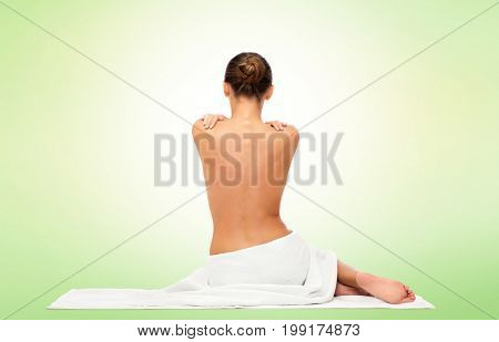 beauty, spa, people and bodycare concept - beautiful young woman in white towel with bare top from back over green background