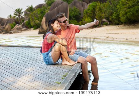 summer holidays, love and people concept - happy teenage couple taking selfie on smartphone and sitting on berth over exotic seychelles beach background