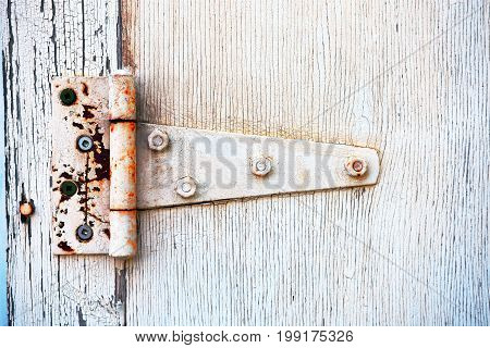 A close up image of an old metal door hinge covered in white peeling paint.