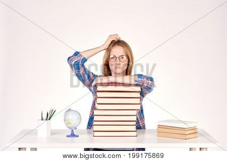 Beautiful teenage schoolgirl sitting at desk with stack of books on it