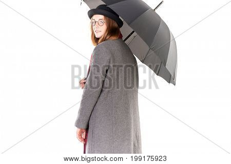 Portrait of teenage hispter girl wearing gray overcoat and holding open black umbrella isolated on white