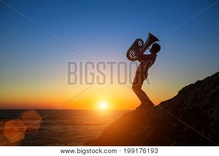 Silhouette of musician play Tuba on the Sea at amazing sunset.