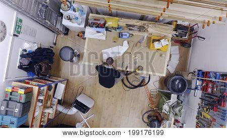 LONDON - AUGUST 2, 2017: Overhead view above a man working inside a workshop interior of a fine art framing business in London, UK.