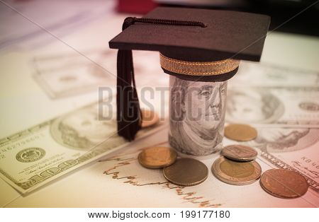 Concept of international graduate study graduation black cap on pile of foreign money US dollars Asian Thai coin Education certificate of Abroad program. Vintage stlye