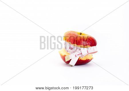Red apple core and measuring tape.The concept of weight control Lose Weight With Fruit Diet concept Adverse effects of excessive weight loss.