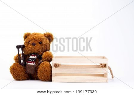 Brown teddy bear holding hourglass isolated And wooden boxes The concept of waiting for someone. Hopefully