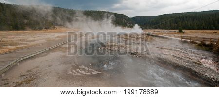 Elevated wooden boardwalk / walkway going past Black Warrior Springs and Tangled Creek and overlooking Hot Lake in the Lower Geyser Basin in Yellowstone National Park in Wyoming United States