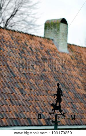 Windvane with hunter and dog opposite the traditional tile roof somewhere in Holland