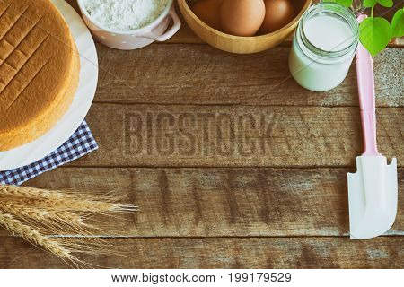 Homemade sponge cake on plate.Soft and lite delicious sponge cake with ingredients: eggs flour milk on wood table.Homemade cake with ingredients with copy space for homemade bakery background concept. Wood plank and sponge cake background.