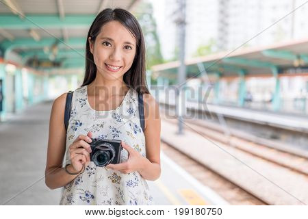 Woman holding camera in light rail station of Hong Kong