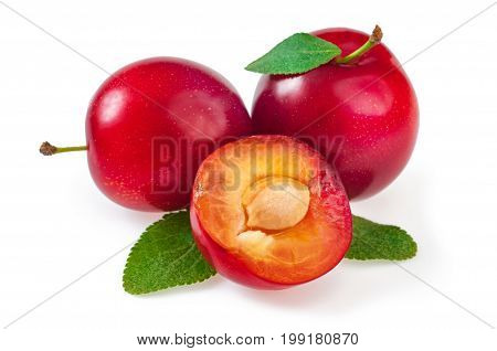 Sweet delicious red plums with leaves and a juicy plum cut into a half. Close-up isolated on white