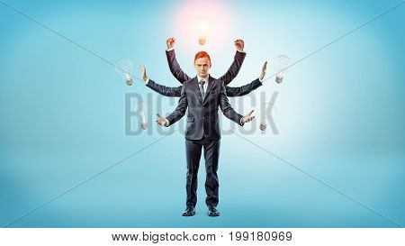 A businessman with many hands surrounded by light bulbs with one of them lighted up. Business ideas. Startups. Business angel.