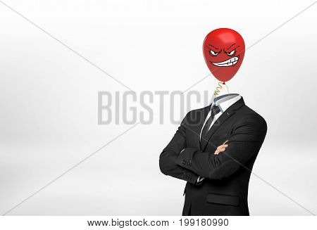 A businessman on white background stands with crossed hands and a red angry face balloon instead of his head. Aggressive leadership. Workplace conflict. Corporate intolerance.