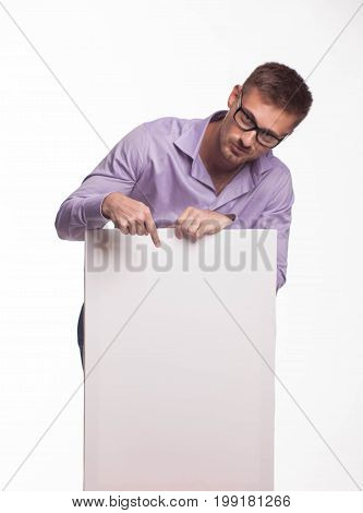 Young jocular man portrait of a confident businessman showing presentation, pointing paper placard gray background. Ideal for banners, registration forms, presentation, landings, presenting concept.