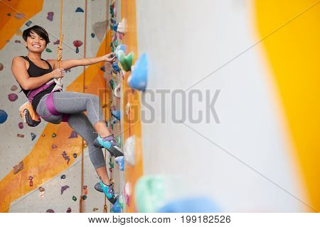 Happy young Asian woman hanging on belay