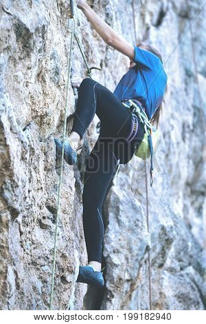 adult woman rock climber. rock climber climbs on a rocky wall.