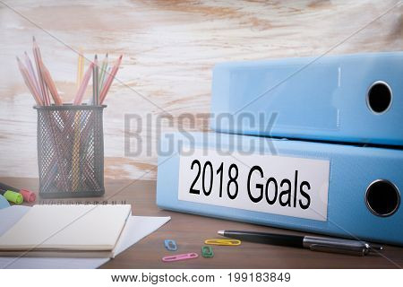 2018 goals, Office Binder on Wooden Desk. On the table colored pencils, pen, notebook paper.
