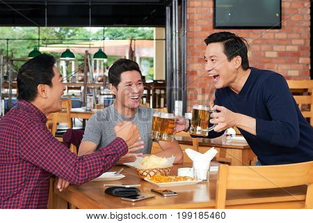 Excited mature Vietnamese man bringing beer to the table of his friends