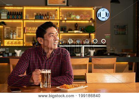 Asian man enjoying beer and snacks in sports bar