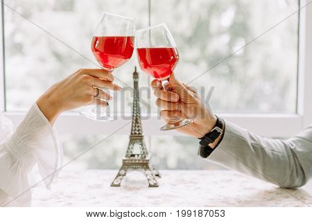 Two people toasting with wine glasses. young couple drinking red wine at restaurant, Beautiful young couple with glasses of red wine in luxury restaurant, happy couple in restaurant looking each other and toasting