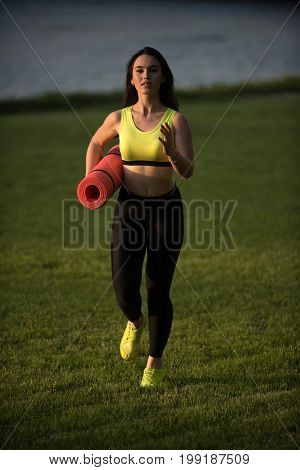 Runner and success. Coach or trainer at workout. Sport and sportswear fashion. Girl sunny outdoor with fitness mat. Woman running on green grass.