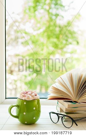 Coffee cup with cream and marshmallows open book and glasses on window with bokeh. Reading and breakfast. Concept cozy home sweet home