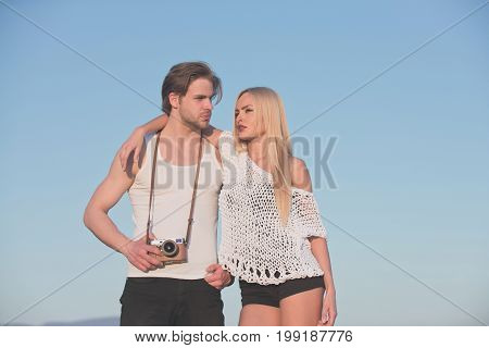 Man with muscular body with girlfriend. Girl with photographer outdoor. Couple in love and romance. Guy with photo camera on athletic chest. Beauty and art fashion.