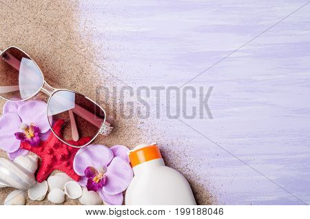Summer holiday background. Beach accessories sunglasses sunscreen and seashells on blue surface top view. Vacation and travel concept. Copy space