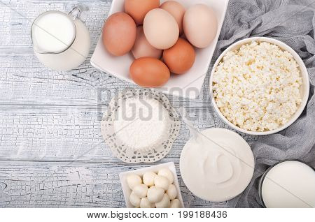 Dairy products on wooden table. Milk sour cream cheese eggs and yogurt. Healthy eating and diet concept. Copy space