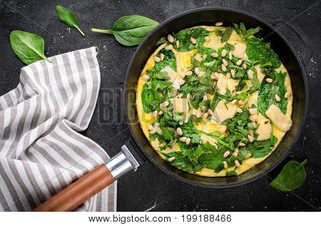 Omelet with eggs spinach pine nuts and vegetables. Spinach tortilla in pan on dark background. Delicious breakfast or appetizer snack. Top view