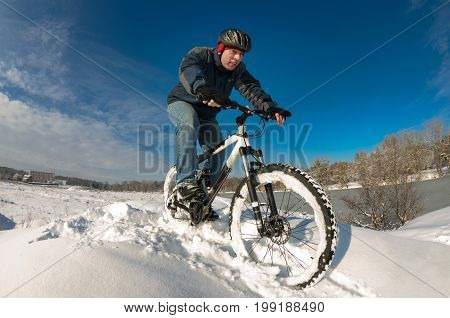 Man enjoys his ride on a bicycle in a deep snow next to the river