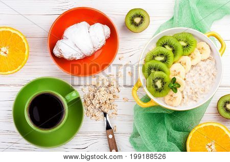 Breakfast with oatmeal porridge croissant fruits and coffee cup. Oatmeal with kiwi orange and banana. Healthy breakfast concept. Top view