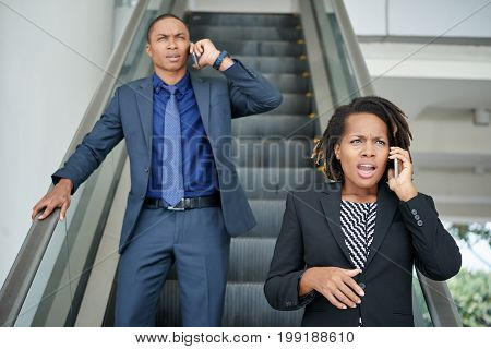 Angry African-American business people calling on the phones when going down the escalator