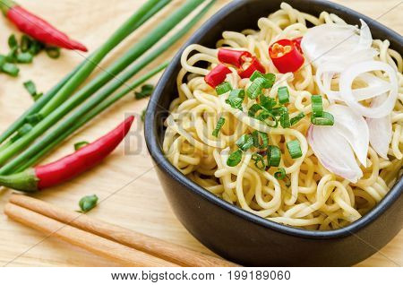 Instant noodles with spicy pepper and onion in a black bowl Asian meal on a table